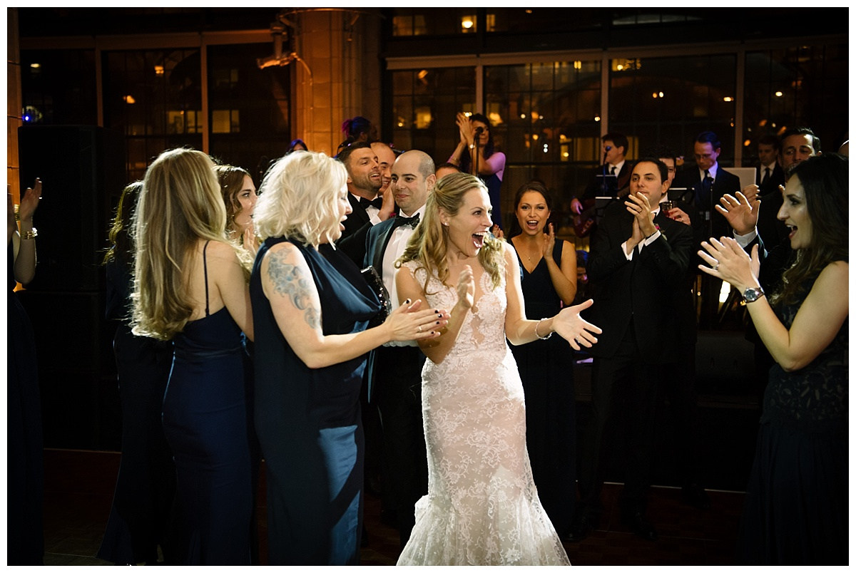 A bride and a groom entering their wedding reception at Guastavinos in New York City. Dress by Ines Di Santo.