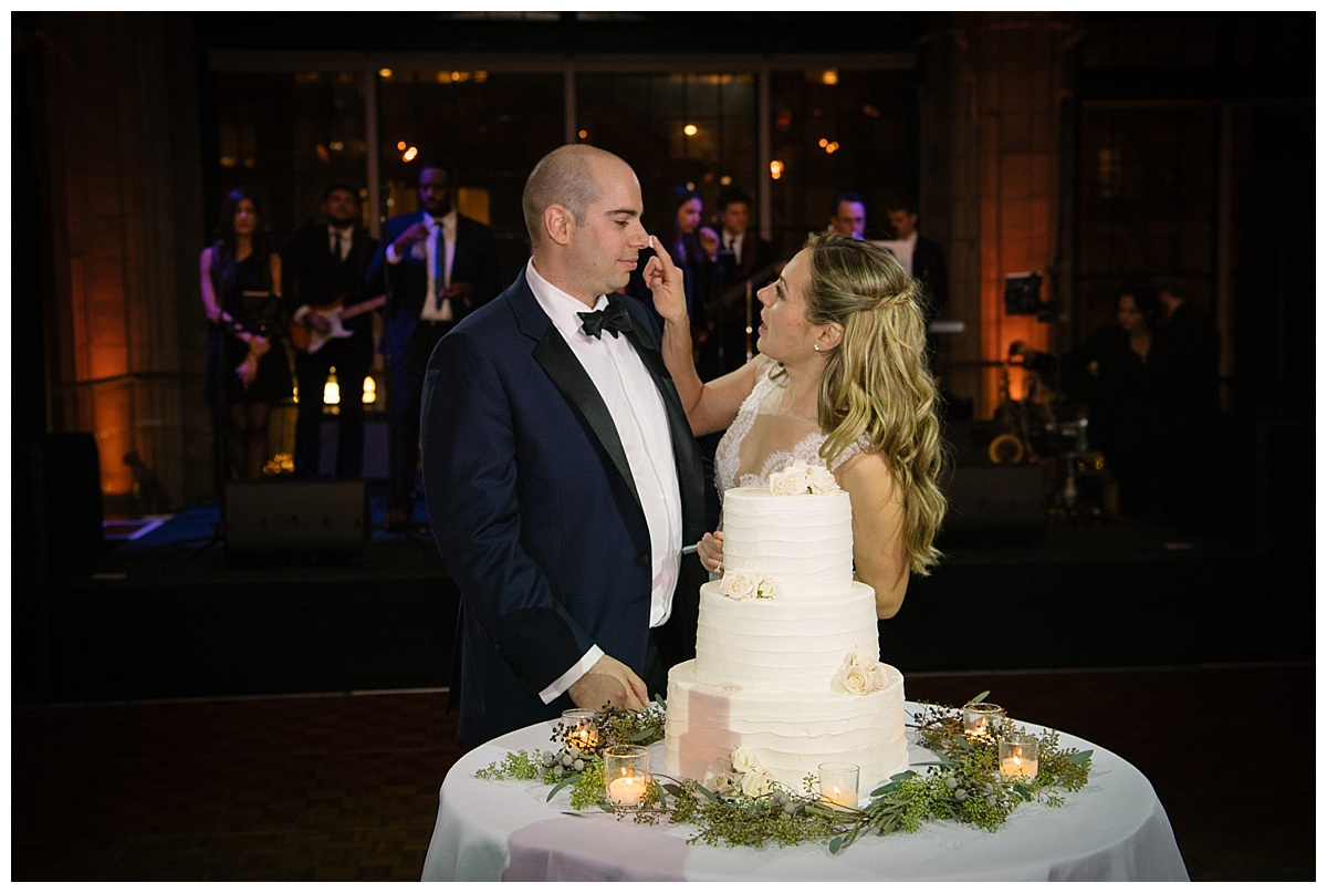 A newly wedded wife putting a cake on her husband's nose during a wedding reception at Guastavinos in New York City. Dress by Ines Di Santo.