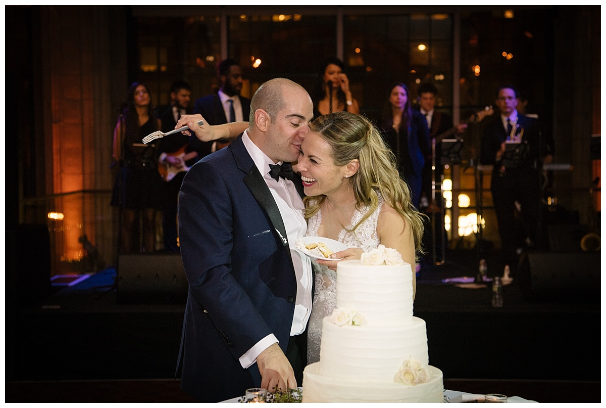 A newly wedded husband kissing his wife next to his wedding cake during a wedding reception at Guastavinos in New York City. Dress by Ines Di Santo.
