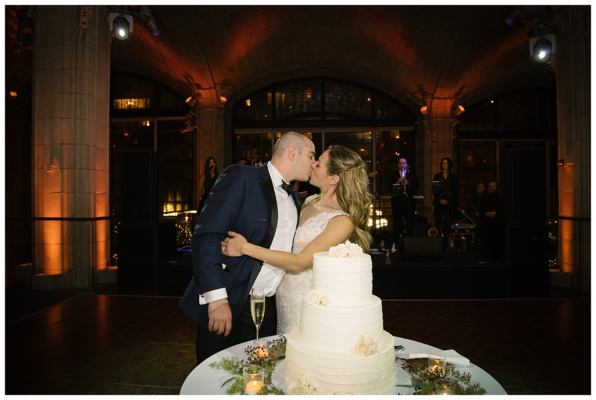 A newly wedded couple kissing behind heir wedding cake during a wedding reception at Guastavinos in New York City. Dress by Ines Di Santo.