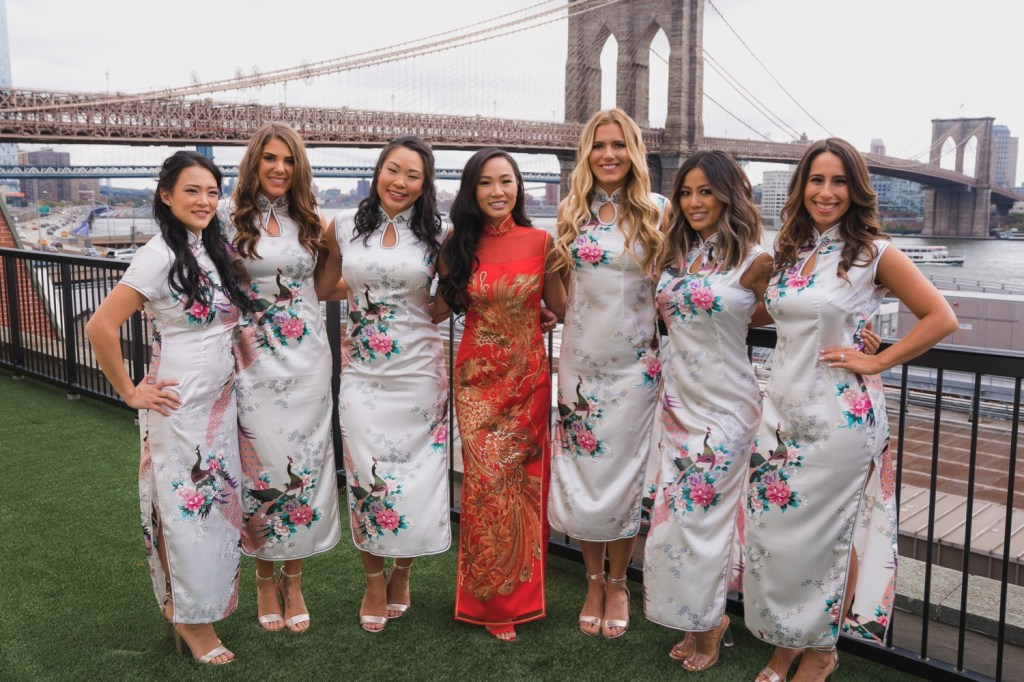 A bride and bridesmaids wearing a chinese dresses with a view of brooklyn bridge in Mr. C Seaport Hotel before Cipriani Wedding in New York City.