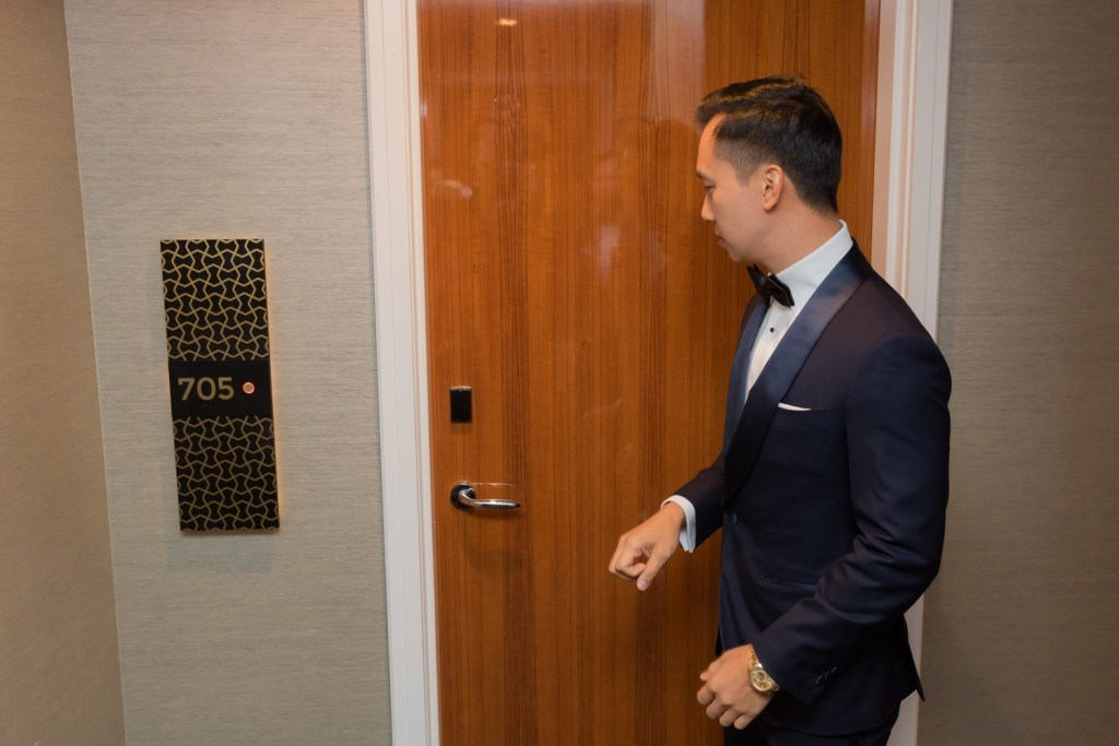 A groom knocking a door to meet his bride in Mr. C Seaport Hotel on a wedding day at Cipriani Wall Street in New York City.
