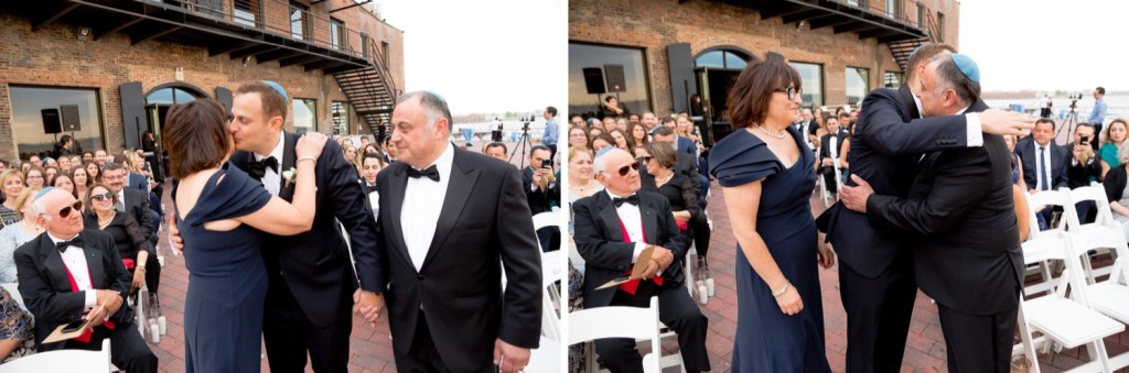 A groom and his parents walking and hugging in an aisle during a wedding ceremony at Liberty Warehouse, Brooklyn New York.