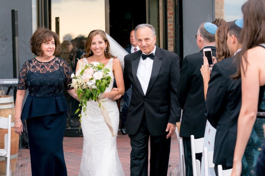 A bride and her parents entering the bride's ceremony at Liberty Warehouse, Brooklyn New York.