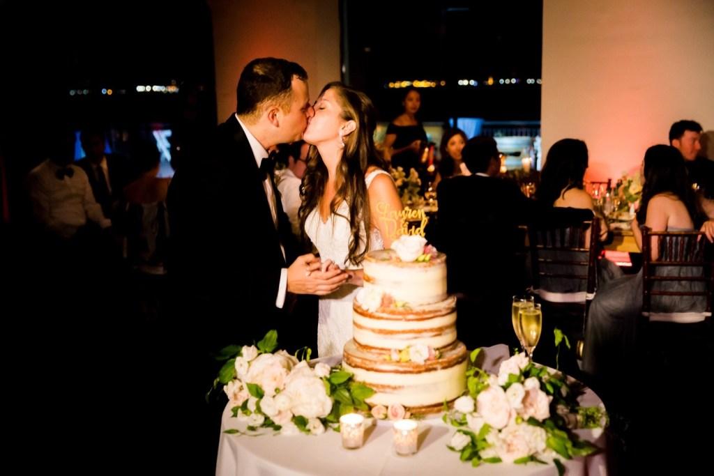 A newly wedded couple cutting their wedding cake during a wedding reception at Liberty Warehouse, Brooklyn New York.