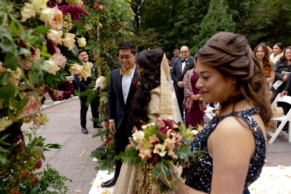 A groom escorting her bride during wedding ceremony starts at the Tappan Hill Mansion.