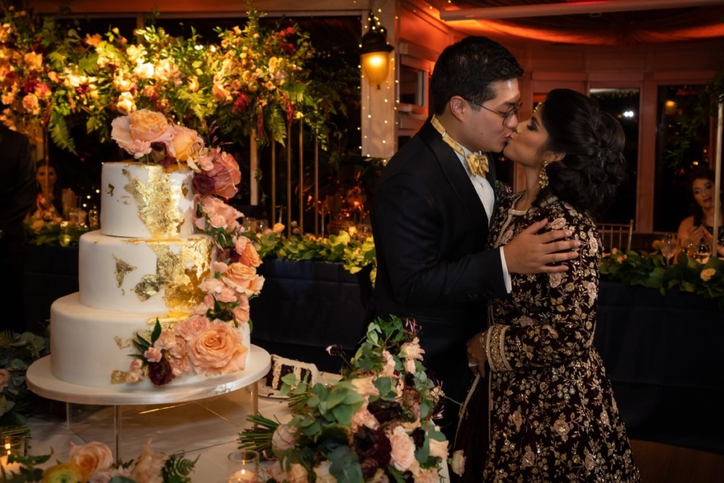 A newly wedded couple kissing next to their wedding cake during a wedding reception at the Tappan Hill Mansion.