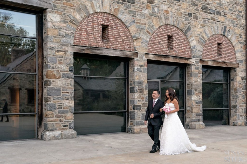 bride and her uncle walking down wedding ceremony at blue hill stone barns