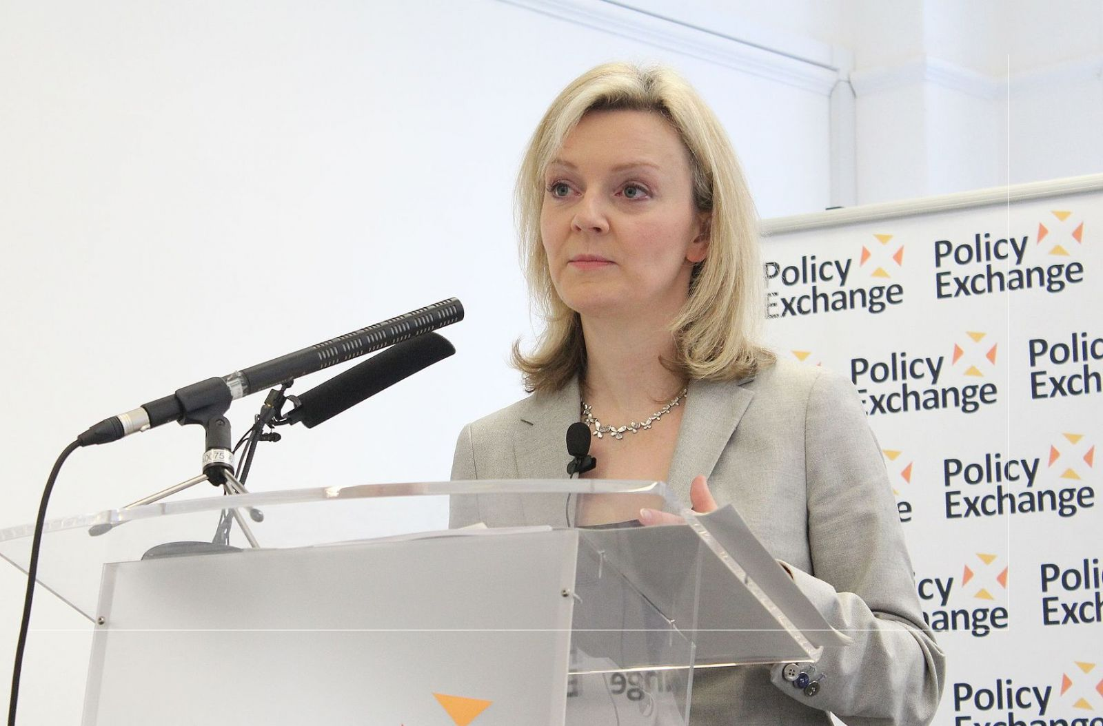 A photo of Liz Truss, current Home Secretary, standing at a podium