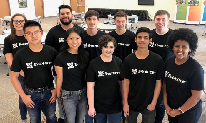 A group of young adults stand, wearing jeans and matching Everence t-shirts.