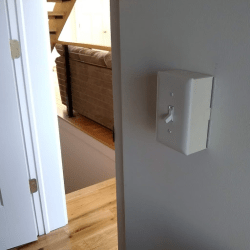 A photo of a light switch where the cover is extended a couple of inches away from the rest of thewall.