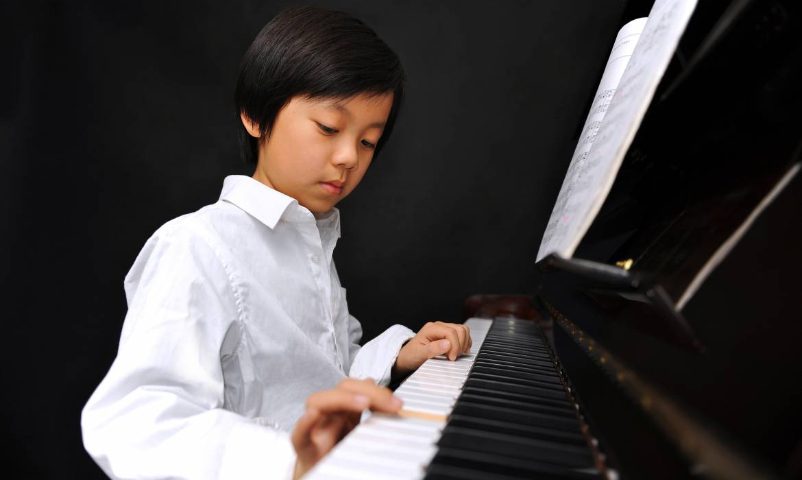 Young Asian boy playing piano against black background