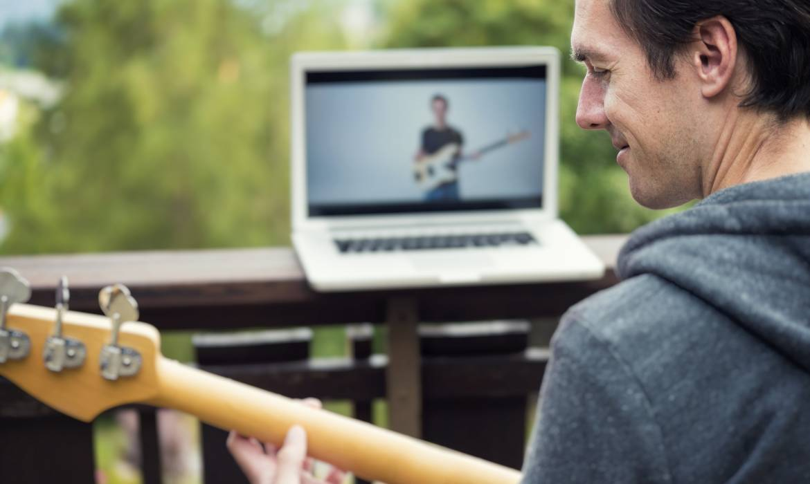 E-Learning and Online Education with a Bass Guitar - the picture seen on the laptop is taken by me as well and shows the same model as in the front of the picture