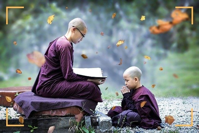 picture of a buddhist sayalay teaching scripture to a young monk boy