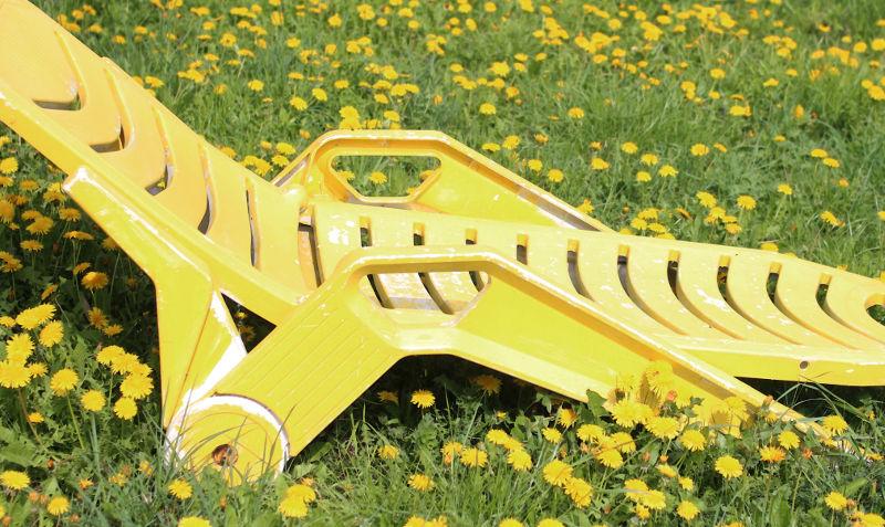 Leben im Wohnprojekt: gelber Liegestuhl auf Löwenzahn