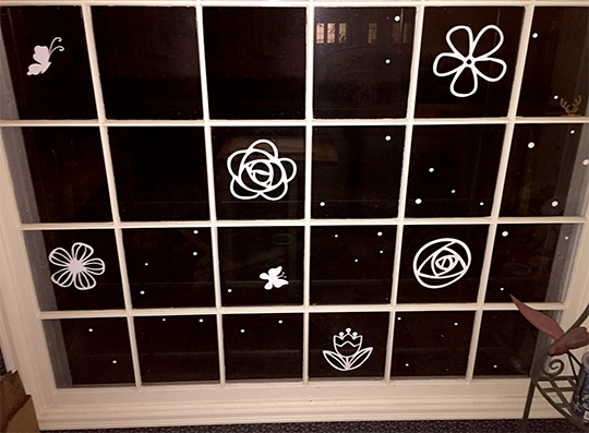 White flowers and butterflies cut from removable contact paper make a seasonal window display