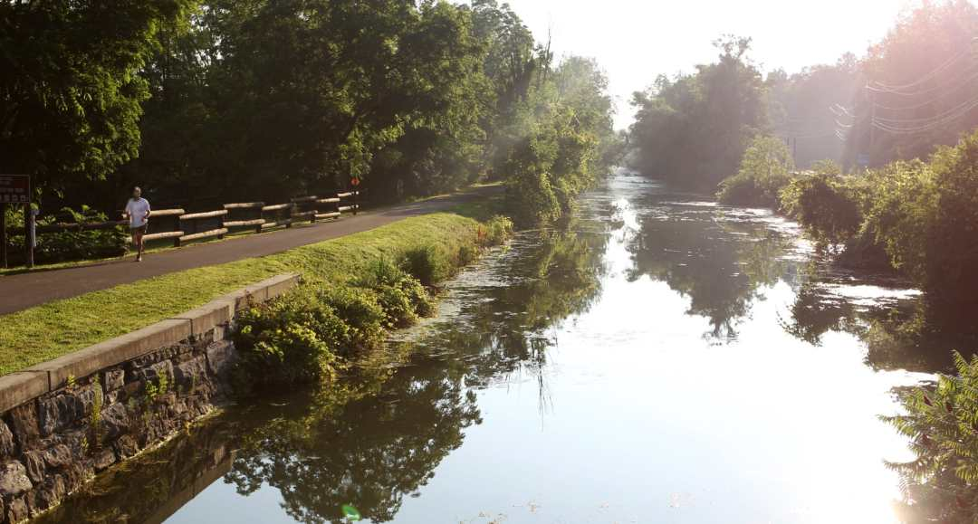 An early-morning jogger runs along the Erie Canal near Green Lakes State Park in Manlius, New York. Morning sunshine streams in through the trees along the future Empire State Trail.