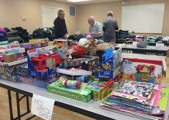 Volunteers sort toys donated to Santa Shop.