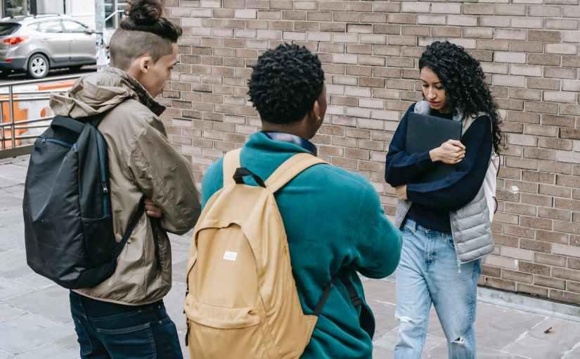 multiethnic friends bullying woman on street