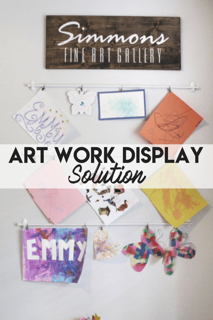 An inexpensive and simple way to display your kids artwork! Made from tension rods and command hooks! Vinyl sign ordered offline for $12! No hole made in the wall either! Easy way to show off your toddlers coloring skills (and free up space on your fridge!)