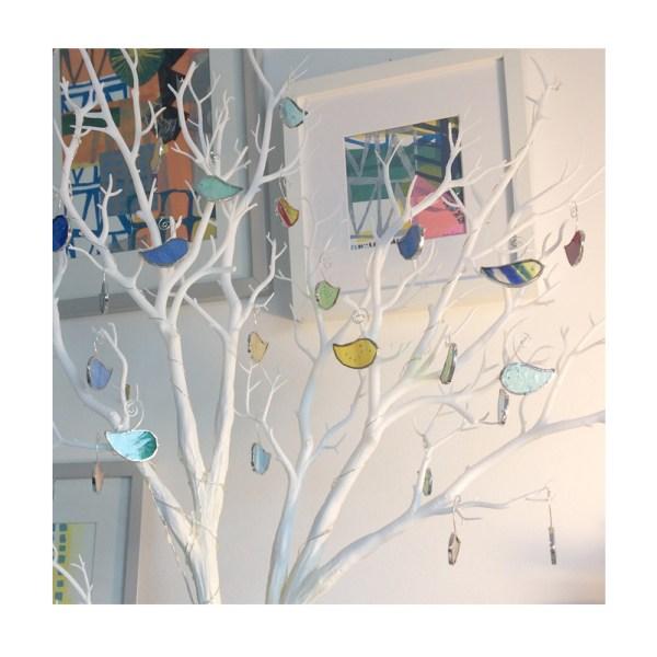 mini glass birds decorating a twig tree