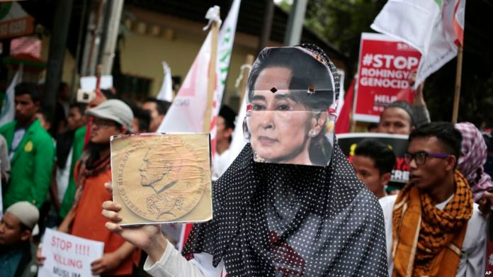A Muslim woman wears a mask of Myanar's Foreign Minister Aung San Suu Kyii during a rally against the persecution of Rohingya Muslims, outside the Embassy of Myanmar in Jakarta, Indonesia, Friday, Nov. 25, 2016. The Myanmar government does not recognize the Rohingya as citizens, though they have lived in the country for generations. Persecution of Rohinyga has escalated in the past several years and they face violence instigated by Buddhist hardl-iners and institutionalized discrimination. (AP Photo/Dita Alangkara)