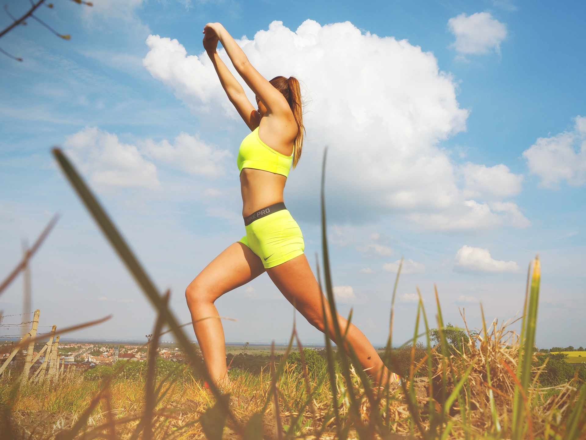 High woman stretching in the field