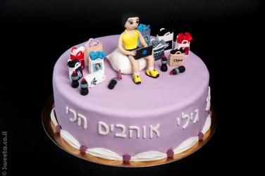 עוגת יום הולדת עם דמות מפוסלת ספורטיבית שקיות שופינג עובדת על מחשב נייד