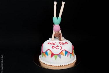 עוגה מבצק סוכר ליום הולדת עם דמות של מתעמלת בתרגיל עמידת ידיים