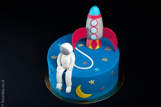 עוגה של אסטרונאוט וחללית מעוצבים מבצק סוכר בחלל עם ירח וכוכבים