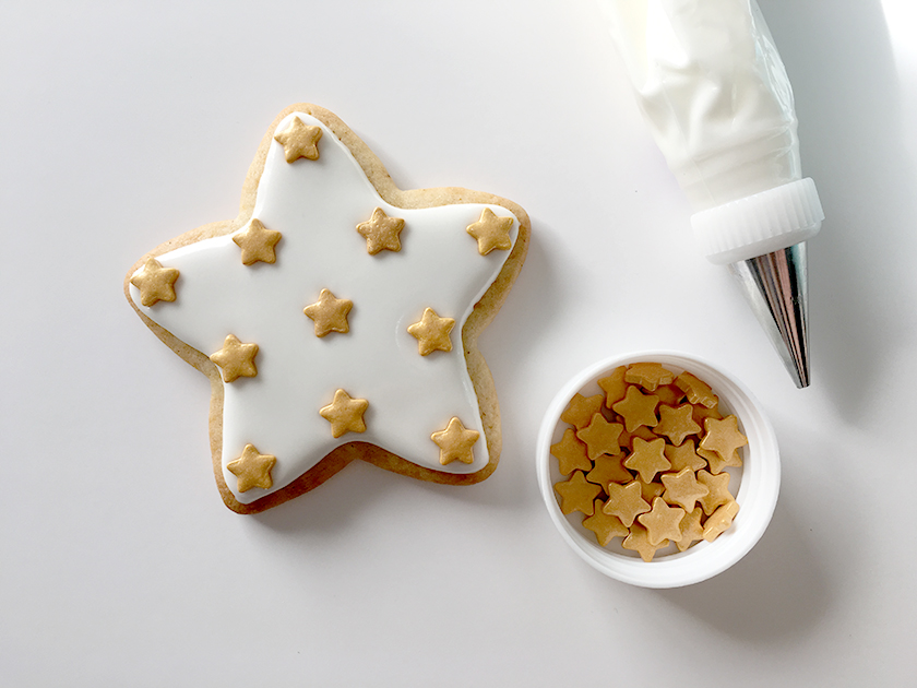 Holiday Cookie DecoratingSweetAmbs 3  Cover a star cookie with white royal icing  Apply Wilton gold star  sprinkles while the icing is still wet  Allow the icing to dry completely