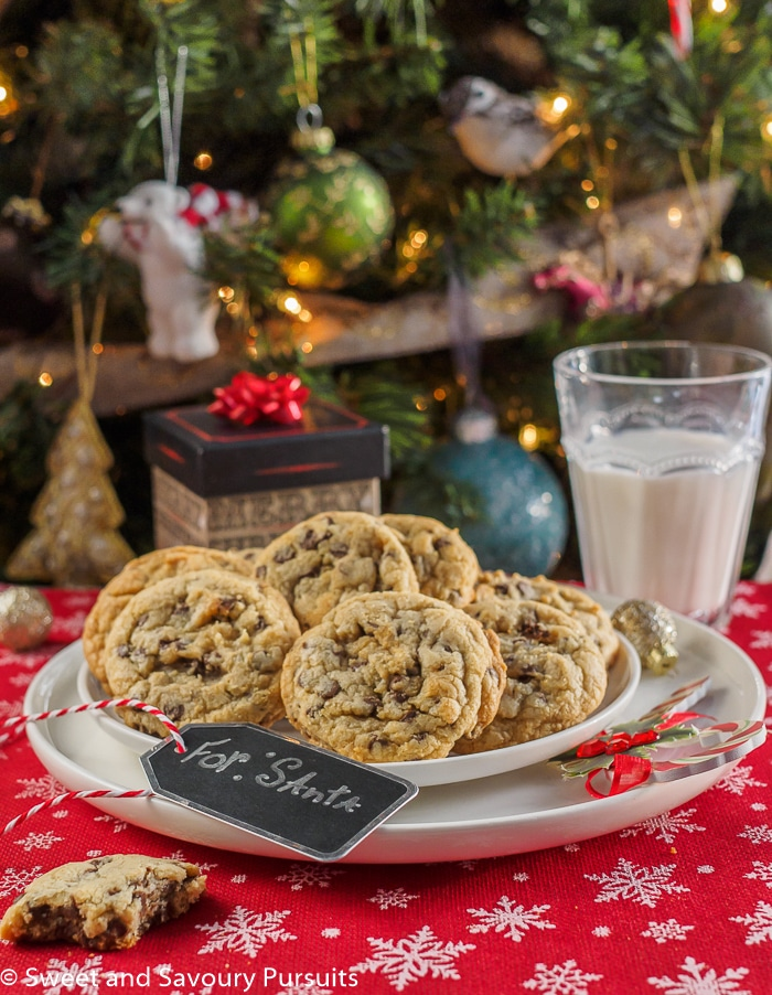 Chewy Chocolate Chip Cookies on white plate with glass of milk