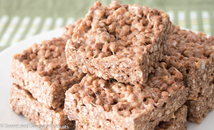Dish of stacked squares made from Cocoa Quinoa Puff cereal and peanut butter.