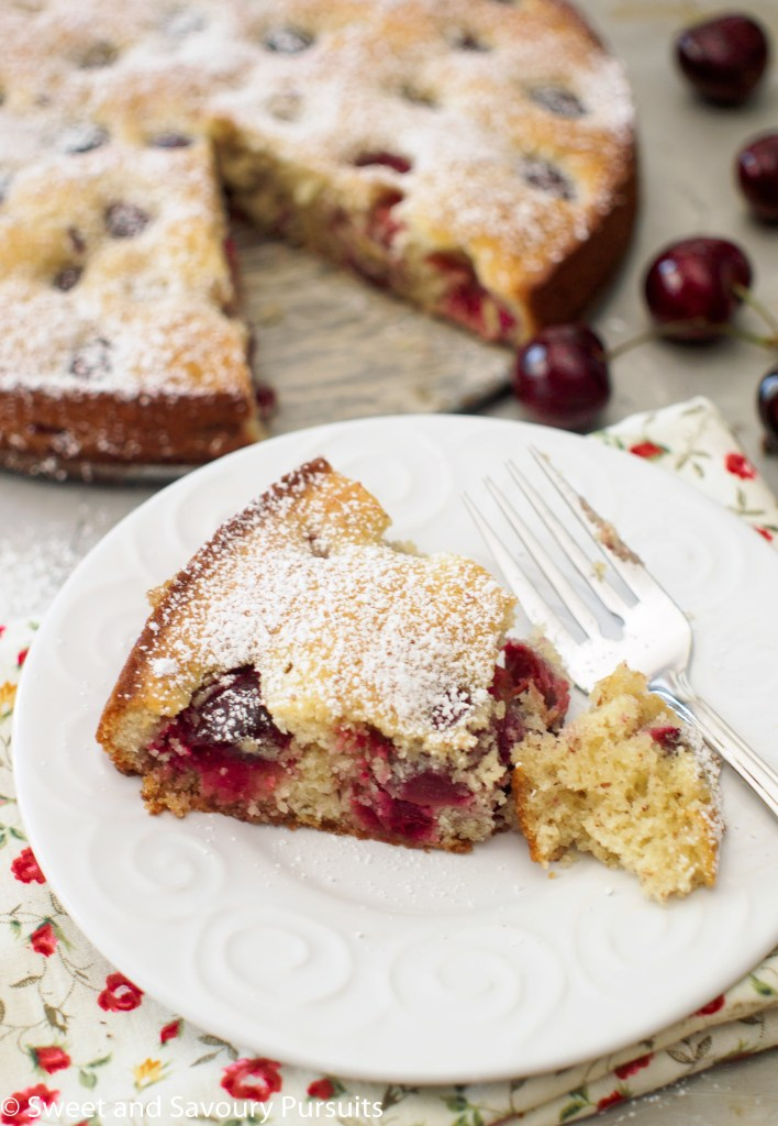 Slice of Cherry Almond Cake with a dusting of powdered sugar on white dish.