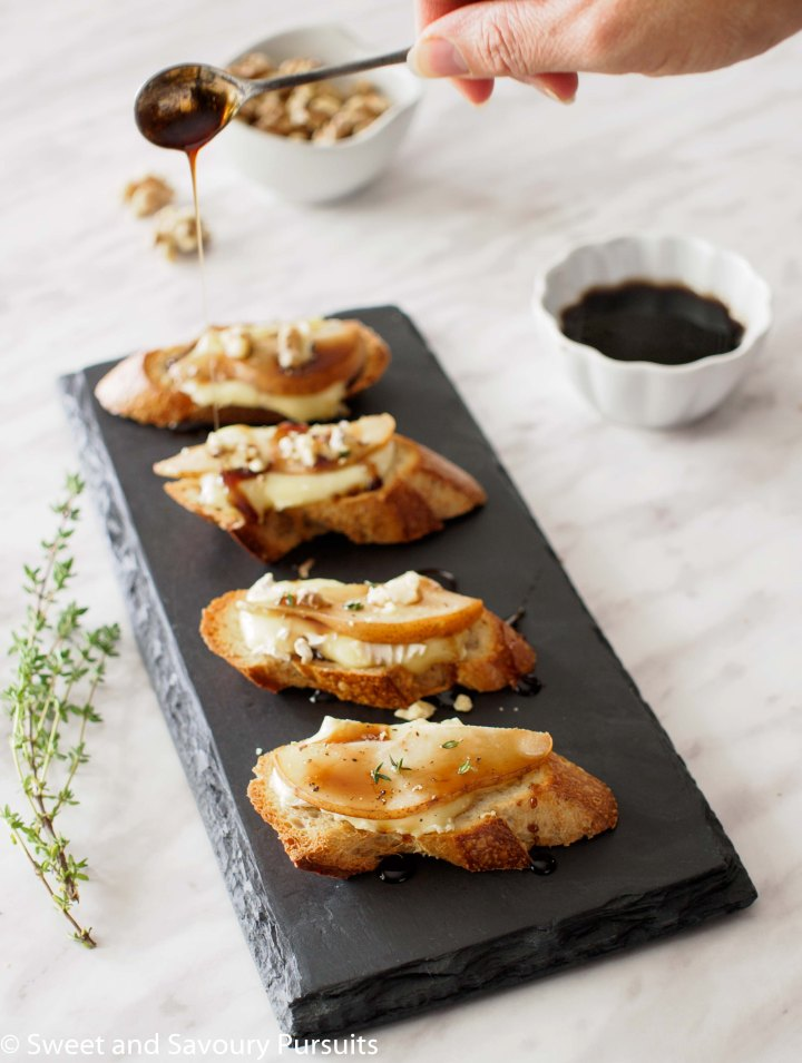 Pear and Brie Crostini topped with balsamic syrup and crumbled walnuts.