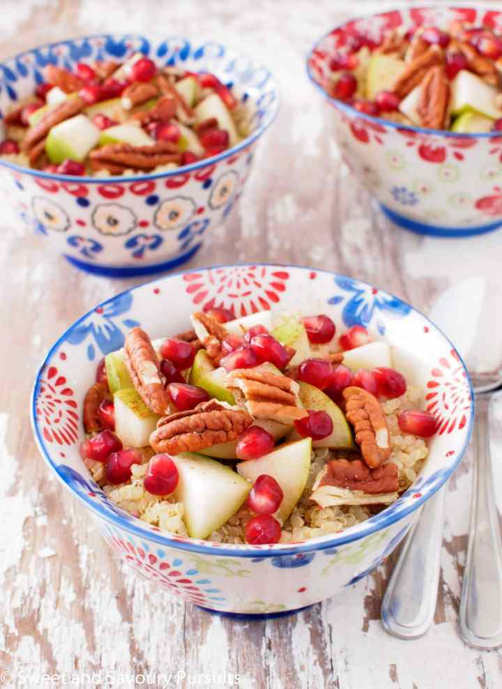Three quinoa breakfast bowls topped with pears, pomegranate and pecans.