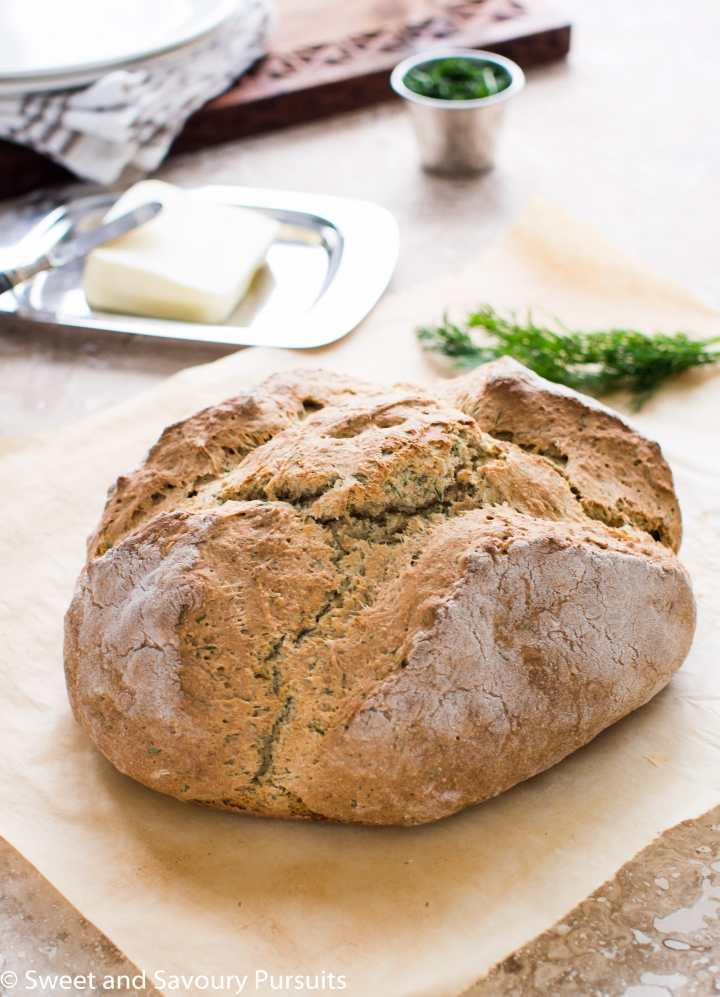 Loaf of Irish Soda Bread with Dill on parchment paper.