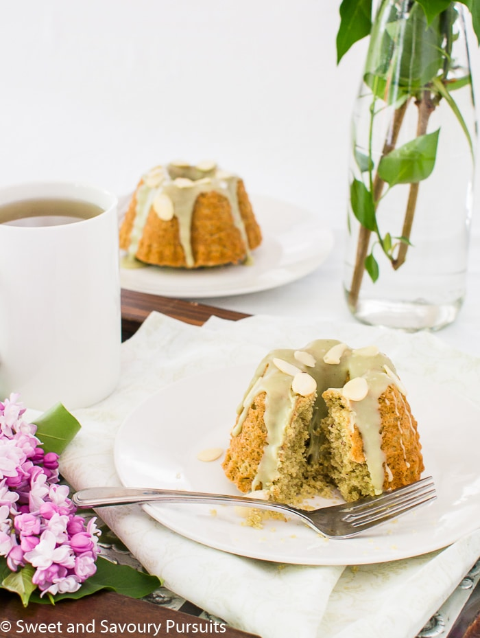 Two small almond and green tea cakes on small dishes.