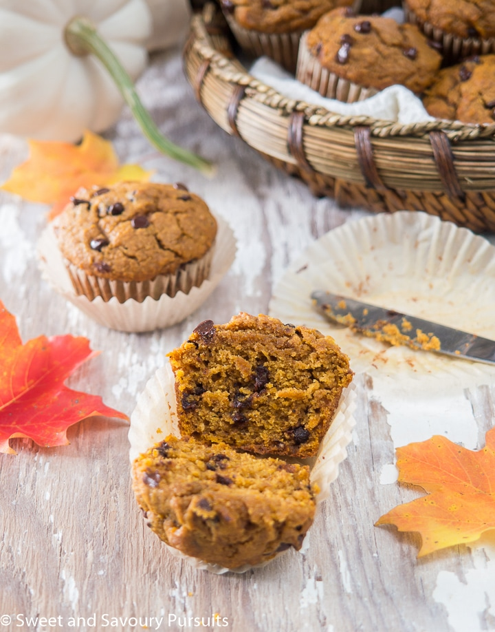 Pumpkin Chocolate Chip Muffin cut in half with more muffins in the background.