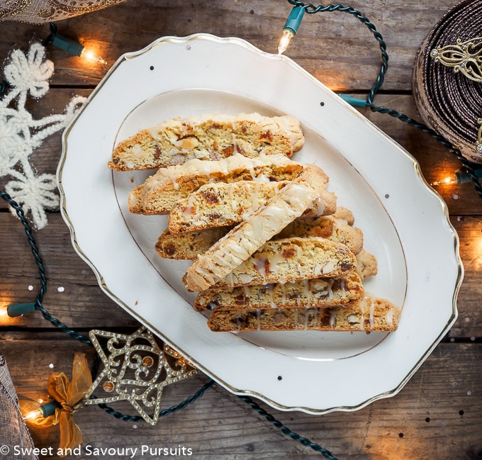 Apricot and Almond Biscotti with White Chocolate Drizzle on serving platter.