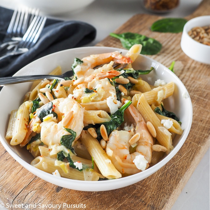 Pasta bowl topped with shrimp, spinach and goat cheese.