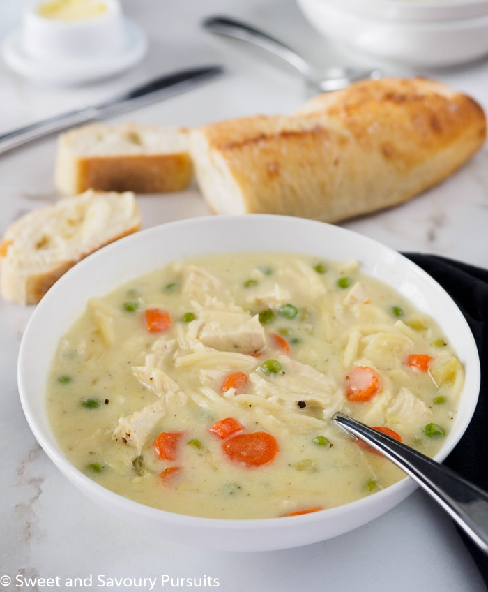 A bowl of creamy chicken noodle soup served with bread.