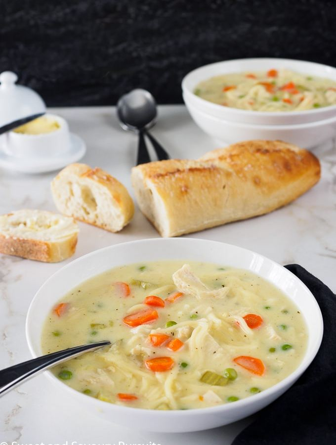 Bowl of Creamy Chicken Noodle and Vegetable Soup served with sliced bread.