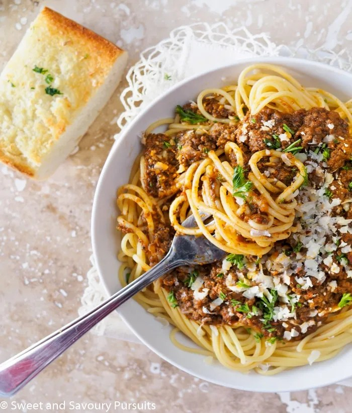 Top view of a bowl of spaghetti and meat sauce with piece of garlic bread on the side.