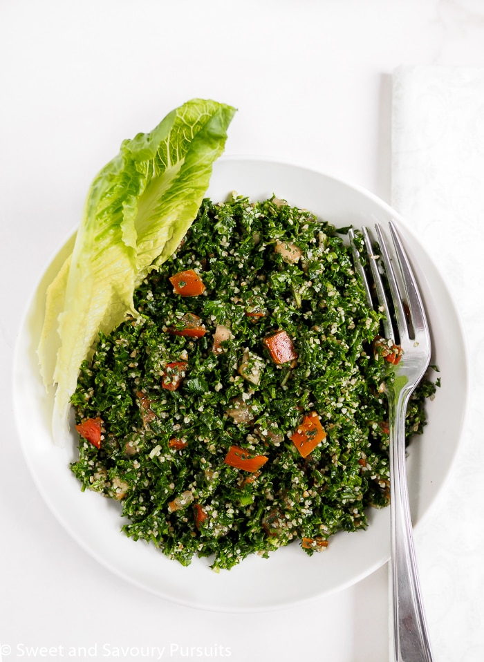 Lebanese Tabbouleh salad served in bowl with romaine lettuce on the side.