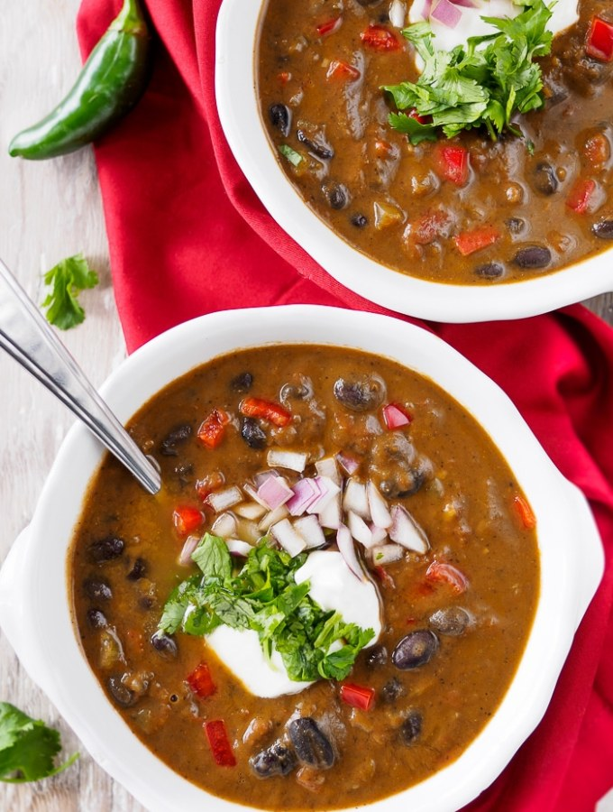 Two bowls of Easy Black Bean Soup topped with sour cream, jalapeno and red onion.