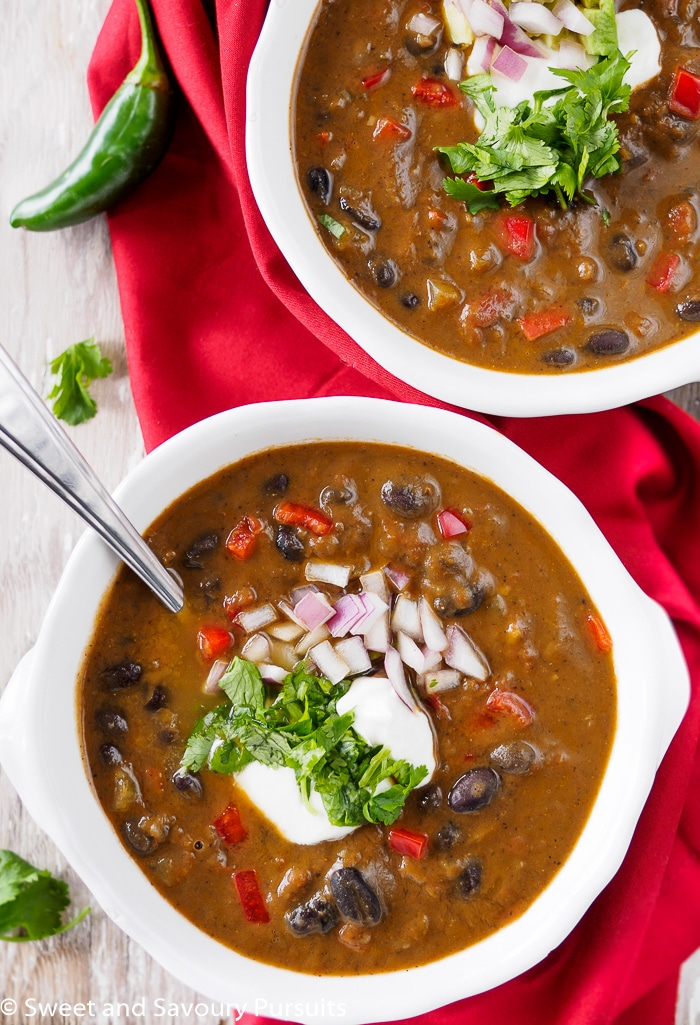 Bowls of Black Bean Soup topped with chopped cilantro, chopped onion and sour cream.