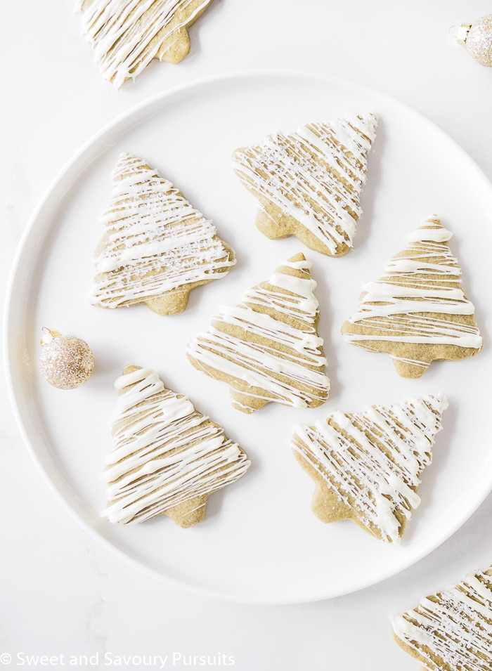 Matcha Green Tea Sugar Cookies drizzled with white chocolate icing on white dish.