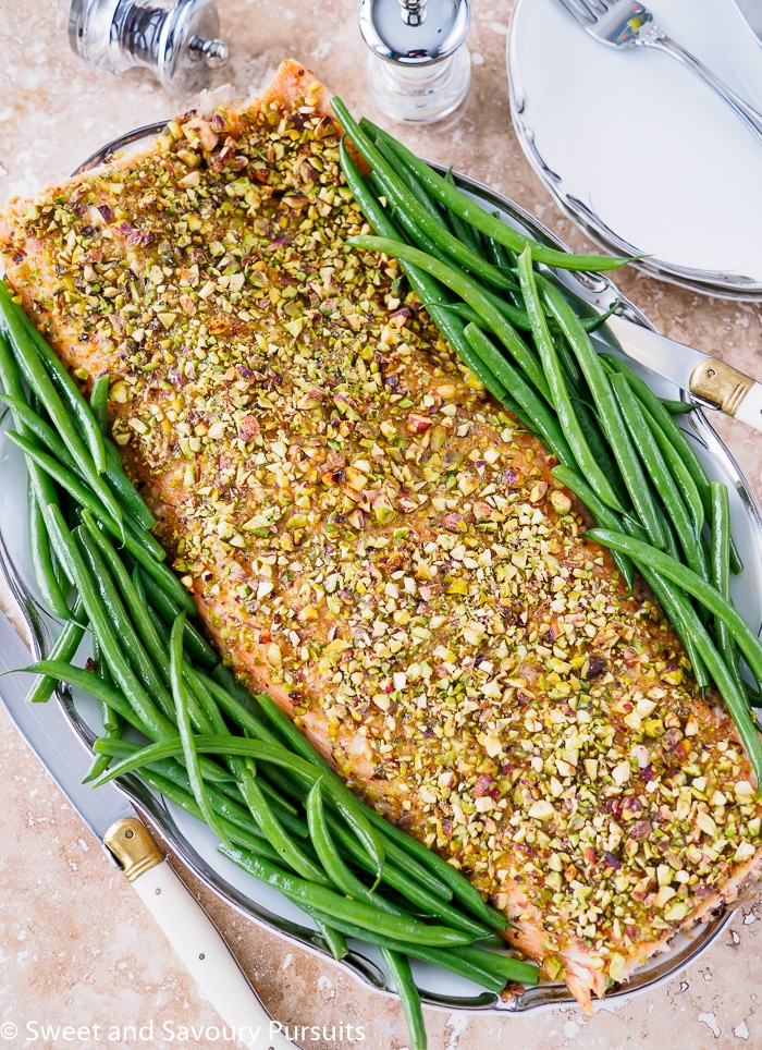 Filet of Pistachio Crusted Salmon on dish with green beans on the sides.