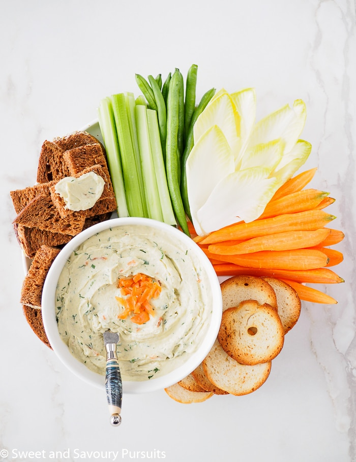 Bowl of Smoked Salmon Cream Cheese Dip served with vegetables, pumpernickel bread and crackers.